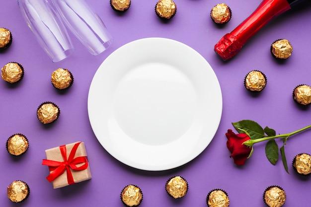 Platliggend arrangement met chocolade en witte plaat Gratis Foto