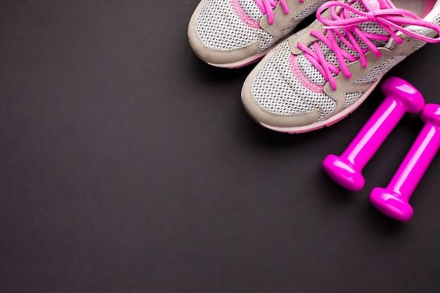 Platliggend arrangement met roze schoenen en halters Gratis Foto
