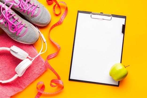 Platliggend arrangement met sportartikelen, klembord en appel Gratis Foto