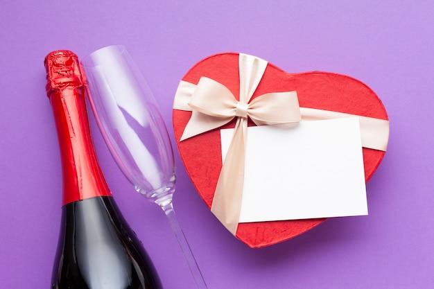 Platliggend arrangement met wijn en hartvormige doos Gratis Foto