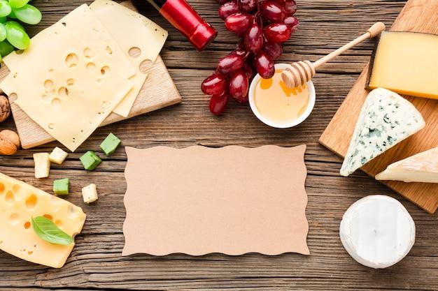 Platliggende kaasmix druiven en honing met blanco karton Gratis Foto
