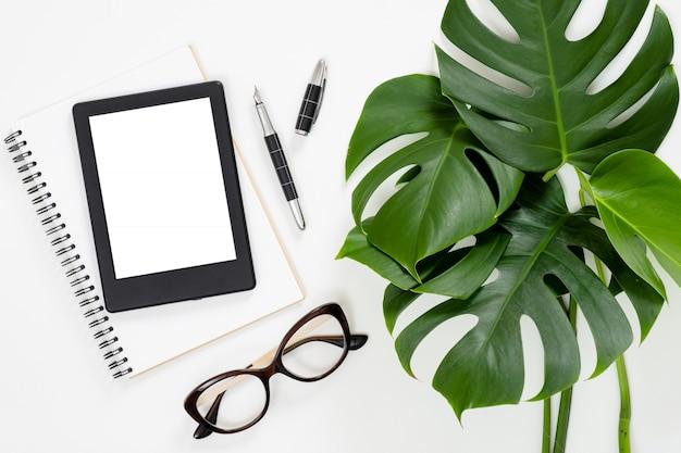 Platliggende tropische jungle monstera-bladeren, papieren notitieboek, e-book reader, bril Premium Foto