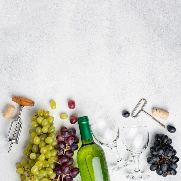 Platliggende wijnflessen druiven met kurkentrekker Gratis Foto