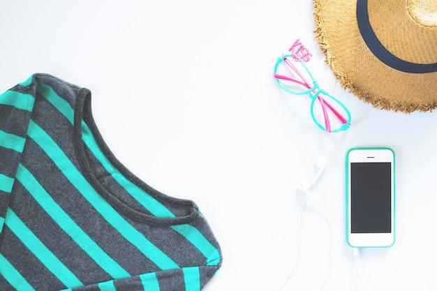Platte lay vrouwelijke kleding en accessoires collage met t-shirt, modebril, hoed met mobiele telefoon en oortelefoon op witte achtergrond. Gratis Foto