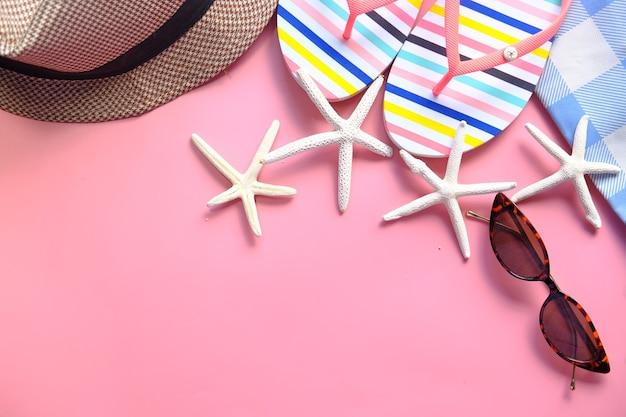 Platte samenstelling van zomer strand accessoires op roze achtergrond. Premium Foto