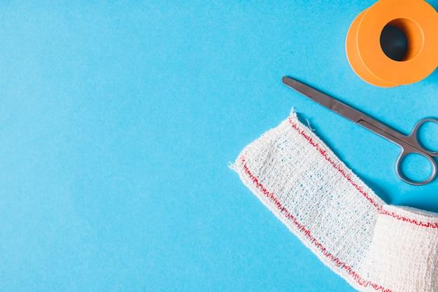 Pleister en katoenen gaasverband met schaar op blauwe achtergrond plakken Premium Foto
