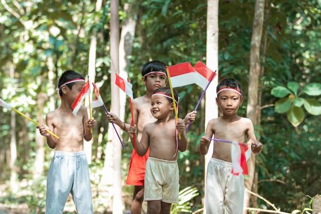 Plezier hebben met een groep kinderen die zonder kleren staan terwijl ze de rood-witte vlag klein vasthouden en de vlag opheffen Premium Foto