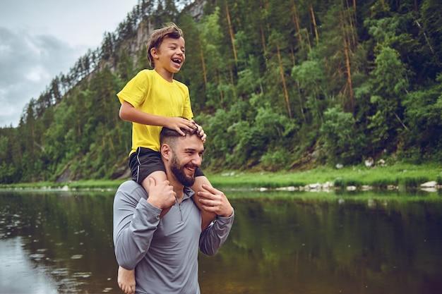 Plezier hebben. vader voorbeeld van nobele mens. kind rijden op vaders schouders. geluk als vader van een jongen. Premium Foto