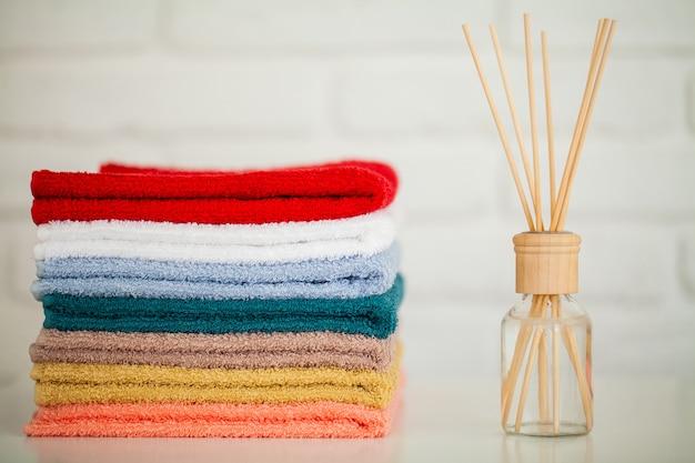 Pluizige badhanddoeken op lichte houten tafel met aromastokken Premium Foto