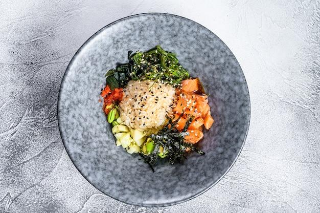 Poke bowl met rauwe zalm, rijst en groenten. grijze achtergrond. bovenaanzicht Premium Foto