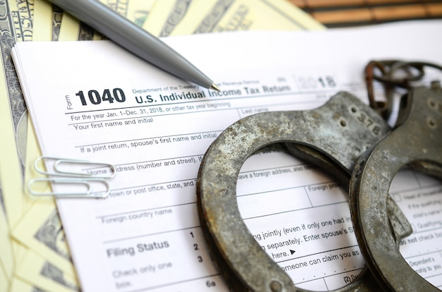 Politie handboeien liggen op het belastingformulier 1040. het concept van problemen met de wet in de nasleep van niet-betaling van belastingen Premium Foto