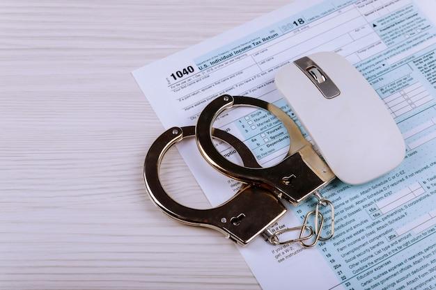 Politie handboeien liggen op het belastingformulier 1040 Premium Foto