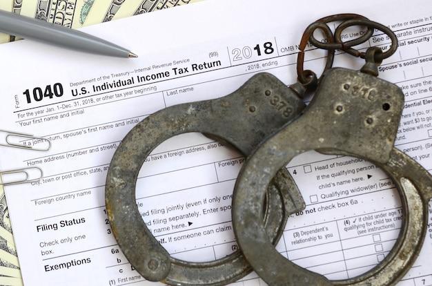 Politie handboeien liggen op het belastingformulier 1040. Premium Foto