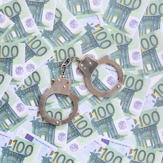 Politie handboeien ligt op een set van groene monetaire coupures van 100 euro. Premium Foto