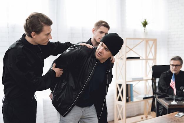 Politieagenten gedetineerde aflevering bij ondervraging. Premium Foto