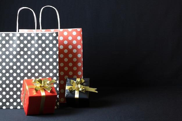 Polka dots papieren zakken met kerst geschenkdozen geïsoleerd op een donkere achtergrond Gratis Foto