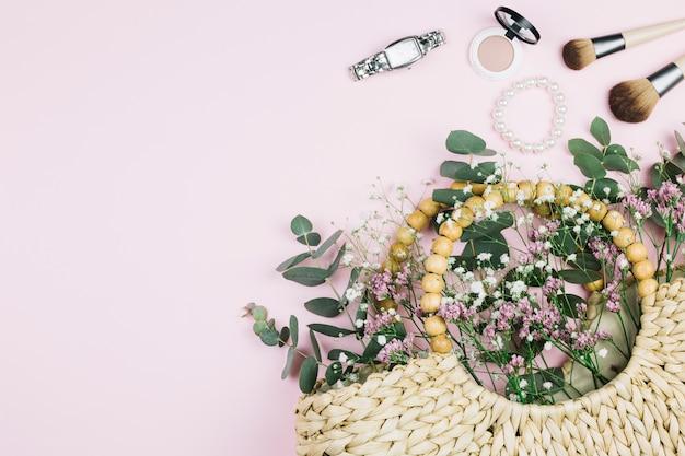 Polshorloge; make-up kwast; parels armband; compact gezichtspoeder met limonium en gypsophila bloemen in de rieten zak tegen roze achtergrond Gratis Foto