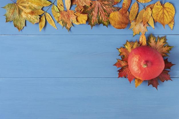 Pompoen en kleurrijke herfstbladeren op blauwe houten tafel Premium Foto
