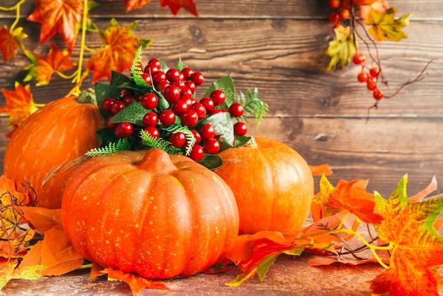 Pompoenen en bessen onder de herfstbladeren Gratis Foto