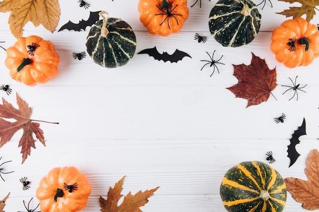 Pompoenen, gedroogd blad, spinnen en vleermuizen op witte houten Premium Foto