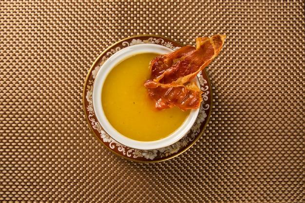 Pompoensoep met prosciutto op tafel Premium Foto
