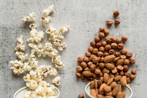 Popcorn en droge vruchten gevallen van kom op concrete achtergrond Gratis Foto