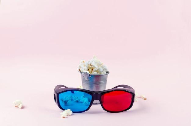 Popcorn in een emmer en 3d-bril op roze Premium Foto