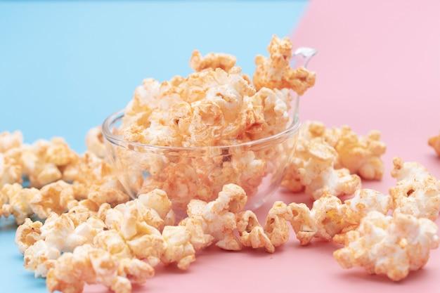 Popcorn in een kom op blauw en roze Premium Foto