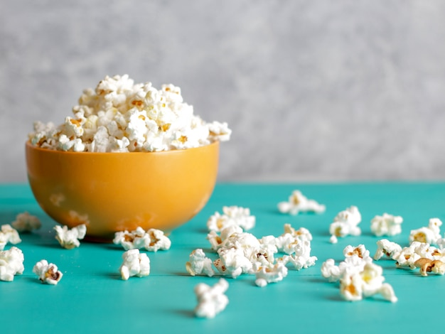 Popcorn in kom op blauw hout Premium Foto