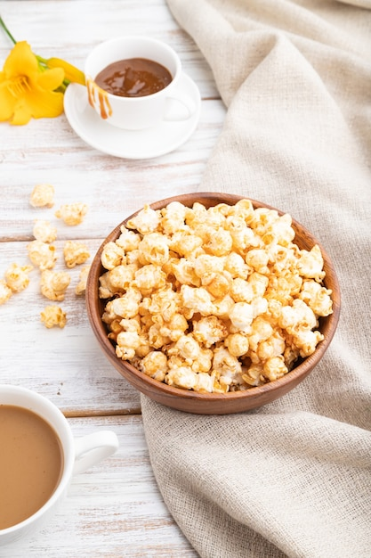 Popcorn met karamel in houten kom en een kopje koffie Premium Foto