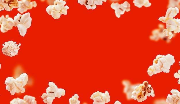 Popcornframe, vliegende die popcorn op rode achtergrond met exemplaarruimte wordt geïsoleerd Gratis Foto