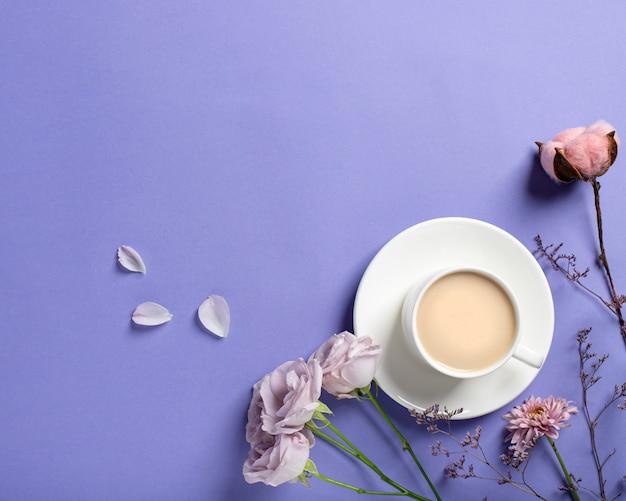 Porseleinen kopje met koffie en mooie lila rozen, gedroogde bloemtakken op een lila achtergrond. lente koffie concept. plat lag stijl, bovenaanzicht, plaats voor tekst Premium Foto