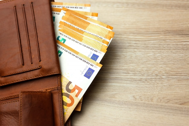 Portemonnee gevuld met eurobankbiljetten op de houten backround Premium Foto