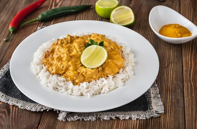 Portie kipcurry gegarneerd met rijst en verse limoen Premium Foto