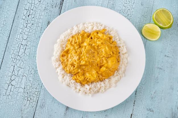 Portie kipcurry gegarneerd met rijst Premium Foto