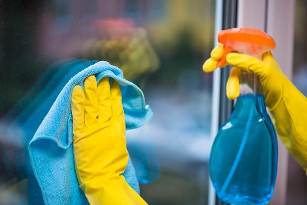 Portier met gele handschoenen die glazen venster schoonmaken Gratis Foto