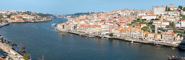 Porto uitzicht op de rivier de douro, boten en oude gebouwen op zonnige dag. porto panoramisch stadsgezicht Premium Foto