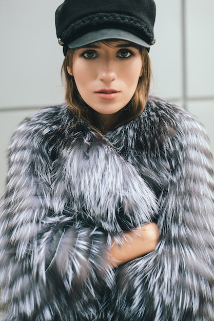 Portrair van modieuze vrouw wandelen in de stad in warme bontjas, winterseizoen, koud weer, zwarte pet, street fashion trend dragen Gratis Foto