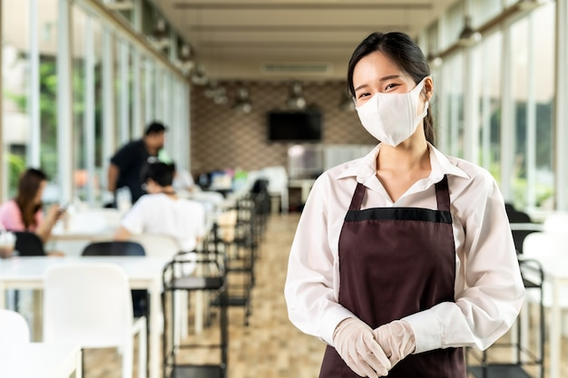 Portret aantrekkelijke aziatische serveerster draagt gezicht met klanten op sociale afstand Premium Foto