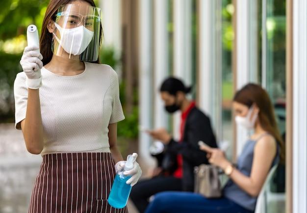Portret aantrekkelijke aziatische serveerster draagt gezichtsmasker en schild houdt thermometer en alcoholgel-ontsmettingsmiddel met achtergrond van sociale distantiërende klant die in de rij wacht. nieuw normaal restaurantconcept. Premium Foto