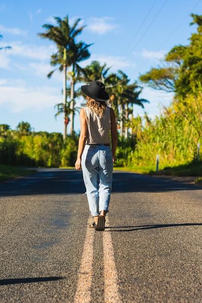 Portret achterkant van prachtige witte vrouwelijke model en lopen op de weg Premium Foto