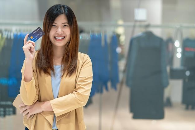 Portret aziatische vrouw die creditcard met slimme mobiele telefoon voor online het winkelen in afdeling gebruiken Premium Foto