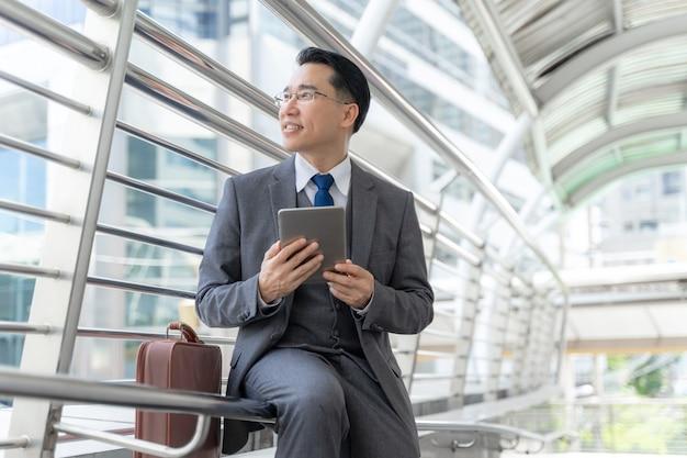 Portret aziatische zaken man zaken district, senior visionaire leidinggevenden leider met zakelijke visionled telefoon computer in de hand - levensstijl mensen bedrijfsconcept Gratis Foto