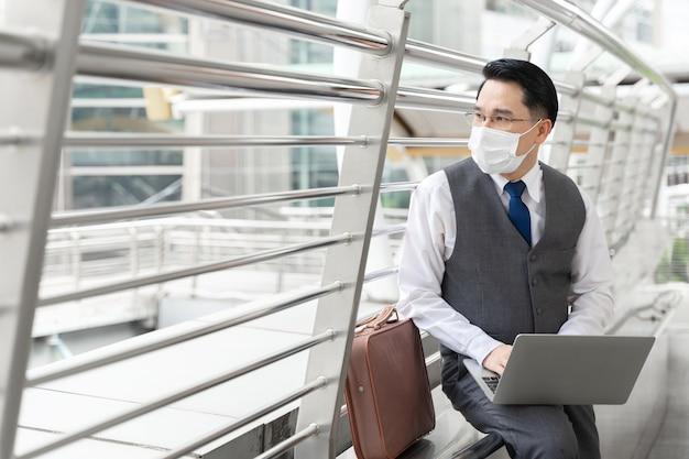 Portret aziatische zakenman die beschermend gezichtsmasker draagt voor bescherming tijdens de quarantaine Gratis Foto