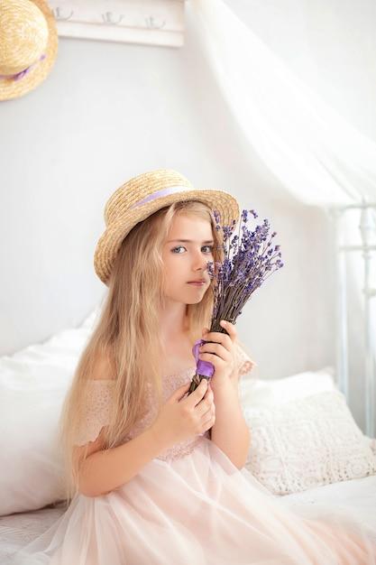 Portret charmante jonge blonde meisje in strooien hoed. meisje met een boeket van slavender in huis. Premium Foto