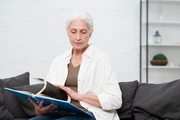 Portret dat van bejaarde een tijdschrift houdt Gratis Foto