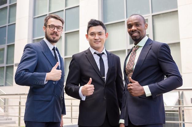 Portret dat van commercieel team hun duimen tegenhoudt Gratis Foto