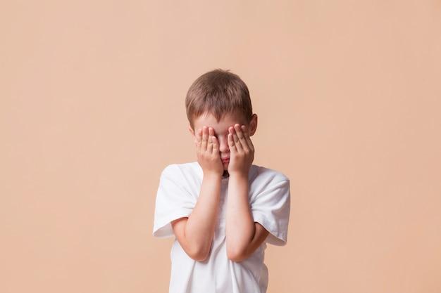 Portret dat van droevige jongen zijn gezicht behandelt met hand Gratis Foto