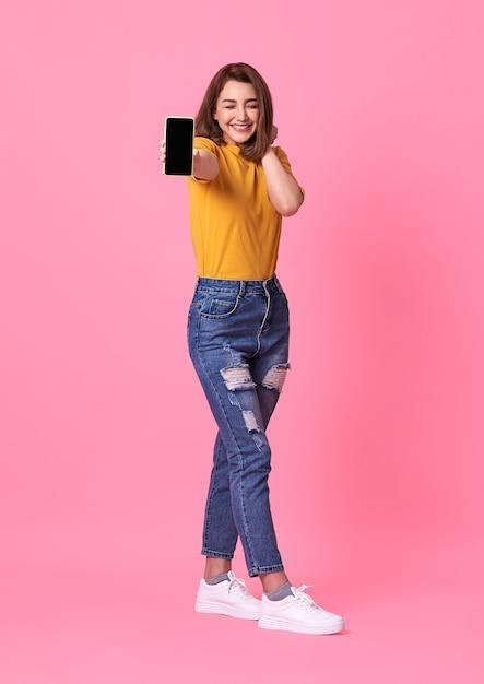 Portret dat van gelukkige jonge vrouw bij lege het scherm mobiele telefoon over roze toont. Gratis Foto