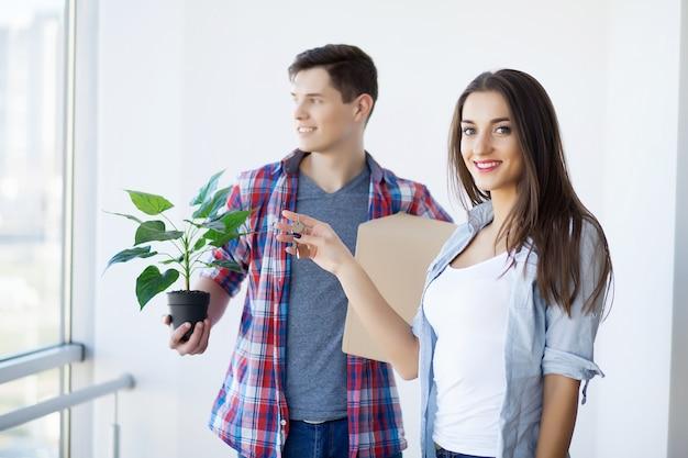 Portret dat van jong paar zich in nieuw huis beweegt Premium Foto
